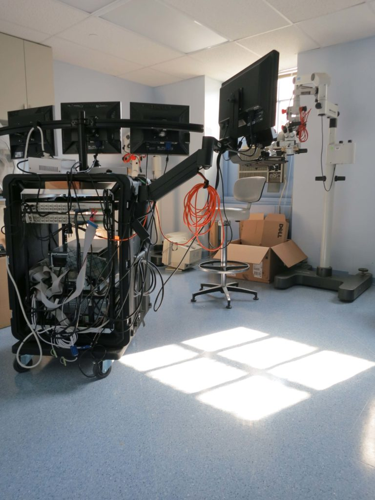 The experimental apparatus. The far right screen is used for video presentation while the others are used for eye tracker calibration and by clinicians.